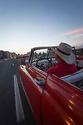 Man in vintage car driving along Malecon road at sunset, Havana, Cuba