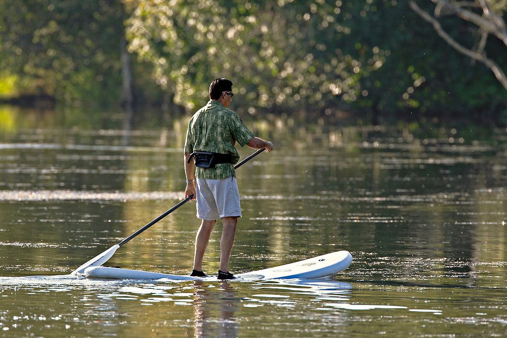 Alaska.  Adult male caucasian riding a stand-up paddleboard in Westchester Lagoon on a sunny morning in early September.