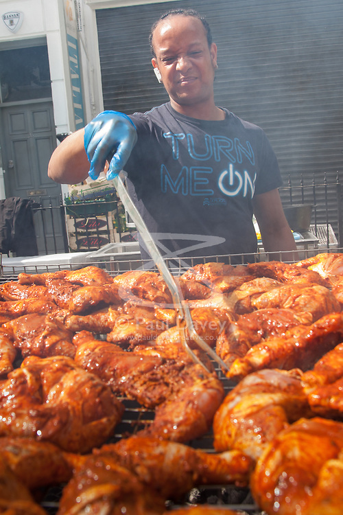 London, August 24th 2014. A man cooks Jamaican jerk chicken as revellers prepare to participate in 2014's Notting Hill Carnival in London, celebratingWest Indian and other cultures, and attracting hundreds of thousands to Europe's biggest street party.