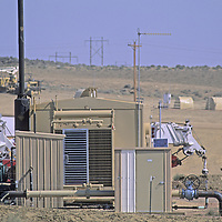 Workers walk by compressors and other equipment at a natural gas drilling site near Sheridan, Wyoming.