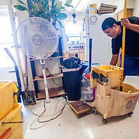 091413       Cable Hoover<br /> <br /> Marsha Dixon helps mop flood waters out of her friend's student housing unit at Navajo Technical University in Crownpoint Saturday.