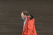 10th March, 2021. Cheltenham, England. A mermber of the publlic walks through the town centre wearing a mask.