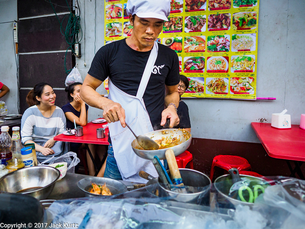 """18 MAY 2017 - BANGKOK, THAILAND: A chef at a street food stall on Yaowarat Road grills prawns. City officials in Bangkok have taken steps to rein in street food vendors. The steps were originally reported as a """"ban"""" on street food, but after an uproar in local and international news outlets, city officials said street food vendors wouldn't be banned but would be regulated, undergo health inspections and be restricted to certain hours on major streets. On Yaowarat Road, in the heart of Bangkok's touristy Chinatown, the city has closed some traffic lanes to facilitate the vendors. But in other parts of the city, the vendors have been moved off of major streets and sidewalks.      PHOTO BY JACK KURTZ"""