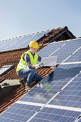 Engineer on roof controlling solar panels