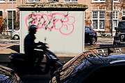 Man op scooter rijdt langs een electriciteitshuis met graffiti.   Man on scooter drives passing an electricity house with graffiti.