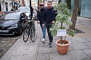 A small sign attached to a plant announces where the Smoking Area is outside a cafe on 15th April 2021 in London, United Kingdom. With the numbers of people smoking tobacco and cigarettes, smoking areas are becomming less common as public health awareness has had a positive effect.