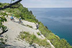 Bikers riding on rocky cliff by sea