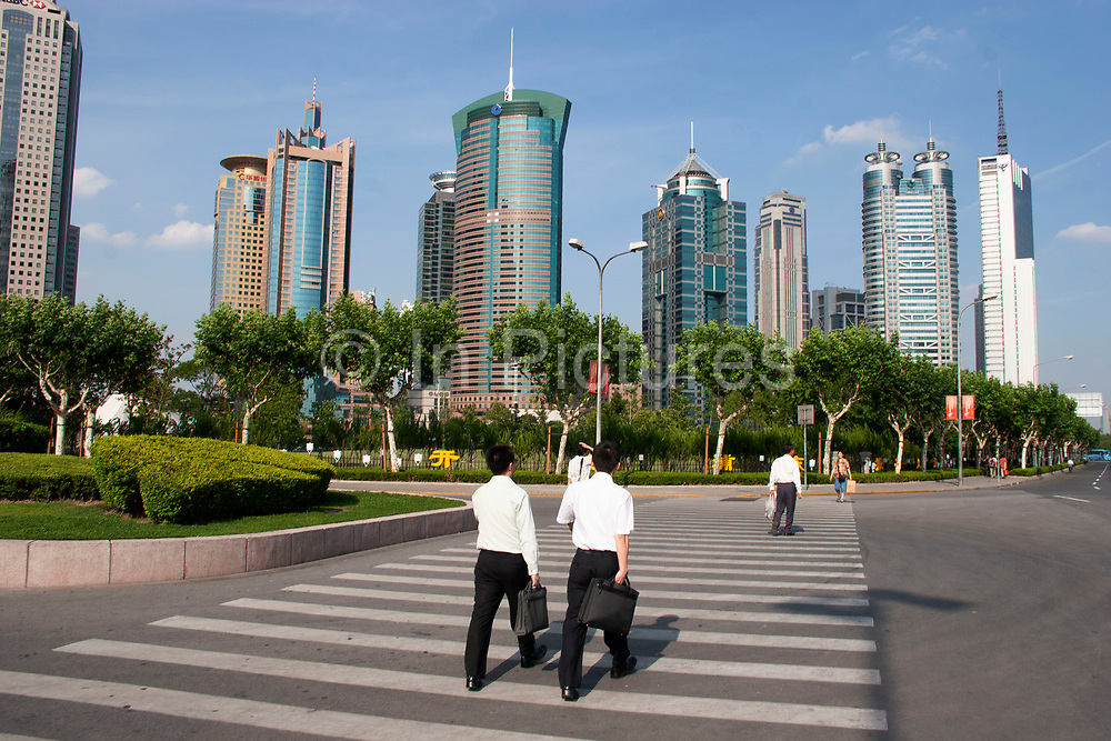 Two businessmen cross the street walking towards Pudong's main financial district Lu Jia Zui. This centre for Shanghai, and even China's finances has developed from nothing since the mid to late 1990's. Now it is a place to see businessmen in crisp white shirts and suits, carrying brief cases.