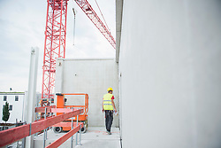Construction worker inspecting the construction site, Munich, Bavaria, Germany, Europe