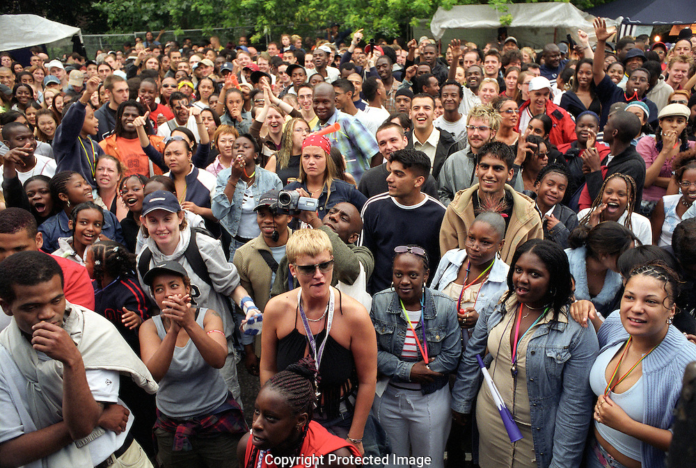 A large multi racial group of people gathered in the streets of Notting Hill at carnival time listening to music..