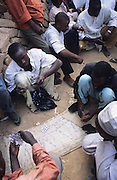 Gambling in the Badawa Ghetto Street Gang on the outskirts of Kano. They are Muslim but drink alcohol, smoke and inject hard drugs..The implementation of Islamic Sharia Law across the twelve northern states of Nigeria, centres upon Kano, the largest Muslim Husa city, under the feudal, political and economic rule of the Emir of Kano. Islamic Sharia Law is enforced by official state apparatus including military and police, Islamic schools and education, plus various volunteer Militia groups supported financially and politically by the Emir and other business and political bodies. Fanatical Islamic Sharia religious traditions  are enforced by the Hispah Sharia police. Deliquancy is controlled by the Vigilantes volunteer Militia. Activities such as Animist Pagan Voodoo ceremonies, playing music, drinking and gambling, normally outlawed under Sharia law exist as many parts of the rural and urban areas are controlled by local Mafia, ghetto gangs and rural hunters. The fight for control is never ending between the Emir, government forces, the Mafia and independent militias and gangs. This is fueled by rising petrol costs, and that 70% of the population live below the poverty line. Kano, Kano State, Northern Nigeria, Africa