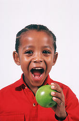 Portrait of young boy eating apple,