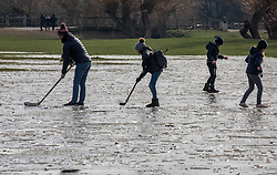 © Licensed to London News Pictures. 13/02/2021. London, UK. A family plays ice hockey on frozen fields that were flooded by Storm Darcy last week. Members of the public gather on the last day of freezing temperatures in Richmond Park, South West London before warmer weather rolls in on Monday with highs of 12c as the government mulls over its road map for unlocking the country from Covid-19 restrictions. Photo credit: Alex Lentati/LNP