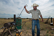 Woodward, OK - Ranch owner Justin Howard removes a hot branding iron while working cattle at his ranch near Woodward.
