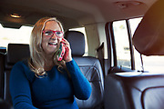 Mature women in backseat of car on mobile phone