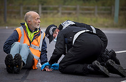 © Licensed to London News Pictures. 20/09/2021. Welwyn Garden City, UK. Climate activist and retired doctor BING JONES being arrested. Protesters from Insulate Britain attempt to blockade the A1M junction 4 near Welwyn Garden City, Hertfordshire. Climate change activists Environmental protest group Insulate Britain have successfully blocked traffic at various points of the M25 on several occasions over the past week. Photo credit: Ben Cawthra/LNP