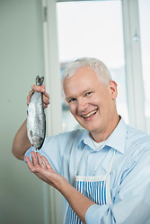 Portrait of mature man holding trout, smiling