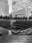 Black and white photo of the 9/11 Memorial in New York City with a section of the names of people who were killed in the foreground