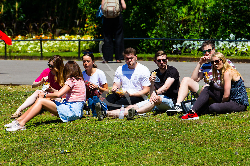 A group of young people enjoy the hot sunshine during lunch hour in Regents Park, London, as the heatwave continues to grip the capital. London, June 29 2018.