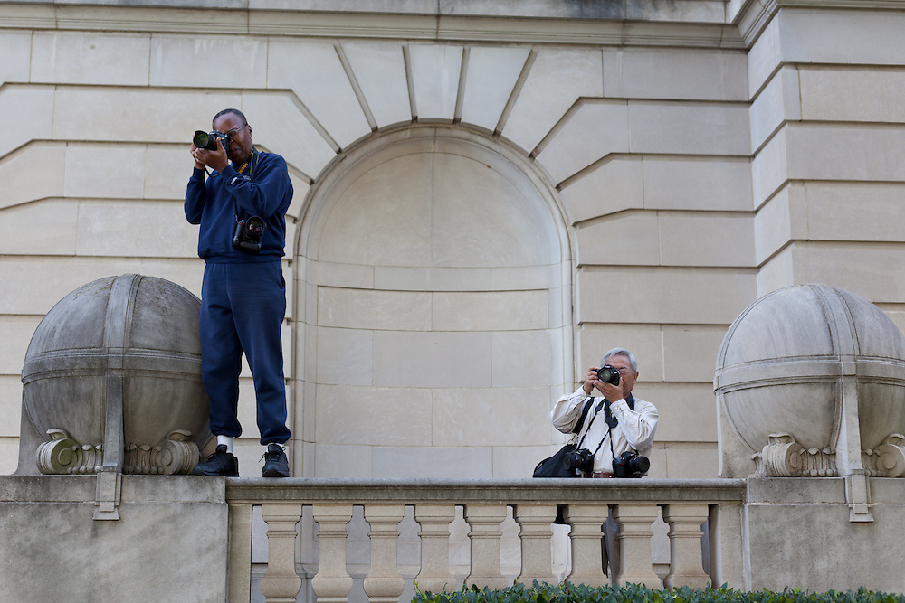 Two photographers photograph the large group of people gathered on the first day of the Occupy Charlotte encampment on old City Hall lawn.