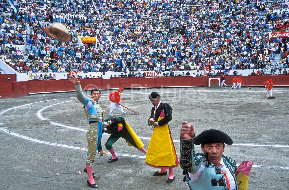 A triumphant Spanish Bullfighter entertains the crowd  and soaks  up their applause and appreciation as he throws into the stands his sombrero after killing the bull in Quito's ring, Ecuador.