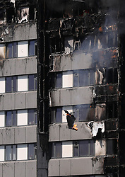 Debris falls from a fire that has engulfed the 24-storey Grenfell Tower in west London.