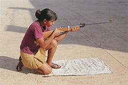 Secondary school girl practising using a gun during shooting lesson,