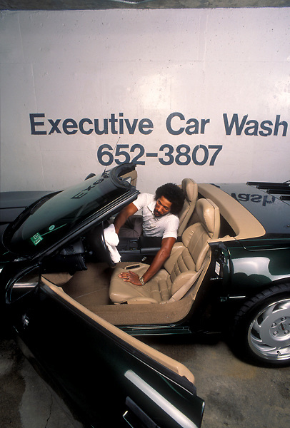 Stock photo of a man detailing the inside of a luxury car