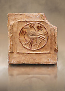 6th-7th Century Eastern Roman Byzantine  Christian Terracotta tiles depicting a bird - Produced in Byzacena -  present day Tunisia. <br /> <br /> These early Christian terracotta tiles were mass produced thanks to moulds. Their quadrangular, square or rectangular shape as well as the standardised sizes in use in the different regions were determined by their architectonic function and were designed to facilitate their assembly according to various combinations to decorate large flat surfaces of walls or ceilings. <br /> <br /> Byzacena stood out for its use of biblical and hagiographic themes and a richer variety of animals, birds and roses. Some deer and lions were obviously inspired from Zeugitana prototypes attesting to the pre-existence of this province's production with respect to that of Byzacena. The rules governing this art are similar to those that applied to late Roman and Christian art with, in the case of Byzacena, an obvious popular connotation. Its distinguishing features are flatness, a predilection for symmetrical compositions, frontal and lateral representations, the absence of tridimensional attitudes and the naivety of some details (large eyes, pointed chins). Mass production enabled this type of decoration to be widely used at little cost and it played a role as ideograms and for teaching catechism through pictures. Painting, now often faded, enhanced motifs in relief or enriched them with additional details to break their repetitive monotony.<br /> <br /> The Bardo National Museum Tunis, Tunisia