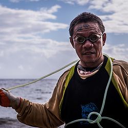 """Severino Mujar """"Saber"""" (nickname because he lacks incisors), the 58 years old veteran diver. Married to Rose, his 5th wife. 2 children. Aside from a heart, he got a Jesus face tattoed his front head which is believed to protect him underwater. He's originally from Surigao. 9 years staying here with Rose and his two children because they couldn't find work in Surigao. Working on site (and living here, in the house right at the beach), since 9 years!! for 5 years out of this 10 years he had been working in an underwater Tunnel. But eventually gave it up since there was no high grades anymore to be found. The tunnel is 30meters long towards the ocean, in dark yellow water. He followed the vein without seeing anything. Only with the squeezing/ shaking pebbles technique to figure out if he found the quartz. """"Philippines is the only country where even the blind can mine"""", jokes Ernie"""
