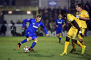 AFC Wimbledon midfielder Dean Parrett (18) taking on two Sutton players during the The FA Cup third round replay match between AFC Wimbledon and Sutton United at the Cherry Red Records Stadium, Kingston, England on 17 January 2017. Photo by Matthew Redman.