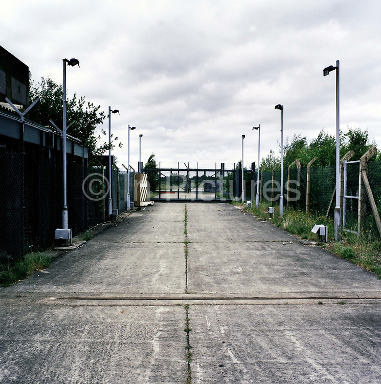 Concrete and fence landscape at the entrance of the former nuclear weapons-era airfield occupied by US Air force personnel during the Cold War and now vacant, awaiting re-landscaping and returning to common parkland for the public to use. Opened in 1942, it was used by both the Royal Air Force and United States Army Air Forces during World War II and the United States Air Force during the Cold War. After the Cold War ended, it was closed in 1993. The airfield was also known for the Greenham Common Women's Peace Camp held outside its gates in the 1980s. In 1997 Greenham Common was designated as public parkland.