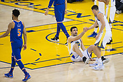 Golden State Warriors guard Klay Thompson (11) helps up Golden State Warriors center Zaza Pachulia (27) during a NBA game against the New York Knicks at Oracle Arena in Oakland, Calif., on May 2, 2017. (Stan Olszewski/Special to S.F. Examiner)