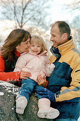 family of three outdoors in The Winter