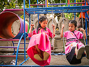 05 APRIL 2013 - CHIANG MAI, THAILAND: Thai girls in traditional clothes play on a swing set at Wat Pa Pao. Their brothers are being ordained as Buddhist novices during the Poi Sang Long festival at the temple. The Poi Sang Long Festival at Wat Pa Pao in Chiang Mai, Thailand, is an annual festival that marks the ordination of boys in the temple as novice monks. Hundreds of people attend the festival, which is marked by the boys wearing garish makeup and being carried through the temple grounds on the shoulders of older men while musicians play drums and cymbals.     PHOTO BY JACK KURTZ