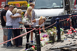 © Licensed to London News Pictures . FILE PICTURE DATED 15/07/2013 . Oldham Street , Manchester , UK . Stephen Hunt's family at the scene . Son Sam (maroon shorts , 15), brother Christopher (white t-shirt, jeans, close cropped hair), grandmother Ruth (blue check shirt, dark trousers , red sunglasses), mother Susan (blue top, beige slacks, sunglasses), stepfather Wilf (dark hair, black t-shirt, grey shorts), daughter Charlotte (black and white sleeveless top, black pants, 18), sister Sarah (cream sleeveless top, blue jeans, dark hair, sunglasses) and ex-wife Zoe (white top, black pants, sunglasses) . The scene on Oldham Street following a fire at Paul 's Hair World on 13th July which claimed the life of fireman Stephen Hunt . Photo credit : Joel Goodman/LNP