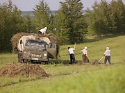 Farm workers loading hay onto an old truck, Perm, Russia
