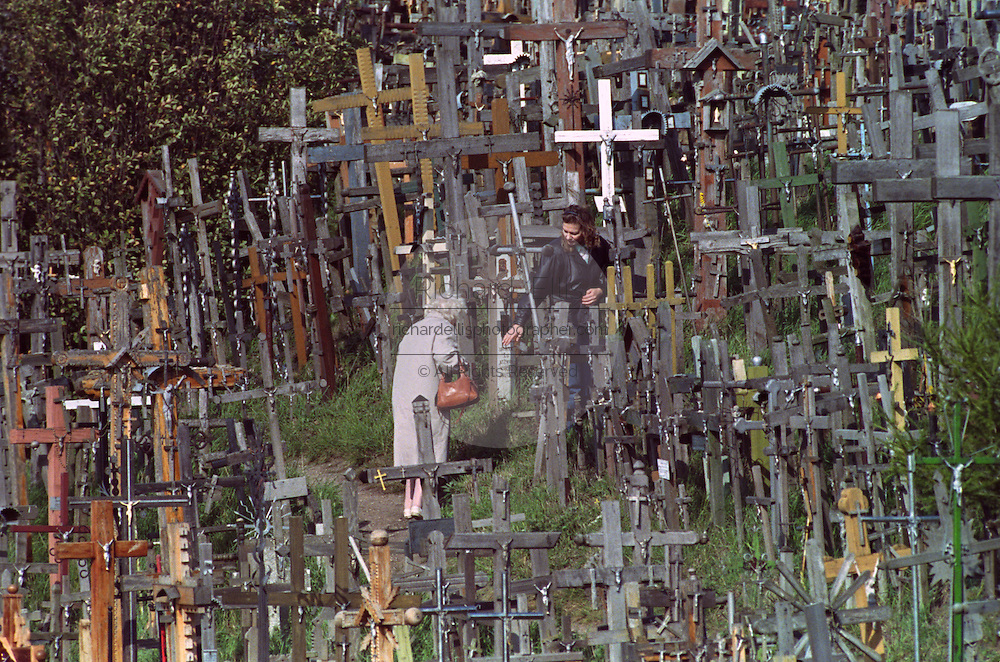 Two women walk through crucifixes left by pilgrims at the Hill of Crosses in Siauliai, Lithuania. The tradition of placing crosses originated as a symbol of Lithuanian defiance against foreign invaders. It is thought to have started during the occupation of Siauliai by Teutonic knights in the 14th century.