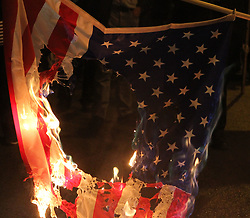 April 17, 2018 - Athens, Greece - Protesters hold a burning U.S. flag during a rally outside the U.S. embassy in Athens. Thousands took part in the rally following the airstrikes in Syria over the weekend. (Credit Image: © Aristidis Vafeiadakis via ZUMA Wire)