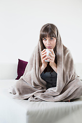 Portrait of mid adult woman covered with blanket and holding cup of tea