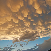 Cumulus thunderheads hover over Montana's Gallatin Valley at sunset.