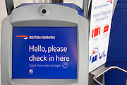"""A close-up detail of one of the British Airways' self-check-in kiosks in international check-in at Heathrow Airport's Terminal 5. A welcome message reads 'Hello, please check in here' and to the right is a guide for cabin baggage size allowance. The self-service kiosks that have been developed to allow customers to process their own ticketing on arrival at this aviation hub for British Airways. Once they've chosen their seat and printed a boarding pass, they can go straight to the Fast Bag Drop desk at the airport. There, baggage will be tagged by an agent and sent to the aircraft. At a cost of £4.3 billion, Terminal 5 has the capacity to serve around 30 million passengers a year. From writer Alain de Botton's book project """"A Week at the Airport: A Heathrow Diary"""" (2009). ..."""