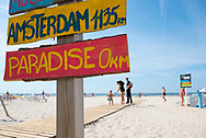 Liepaja, Latvia - August 23, 2015: A sign marks the distances to several cities around the world from the beach in Liepaja, Latvia