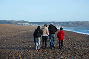 A prisoner released on license walking on Chesil beach, Dorset with his family. Portland is in the background. HMP/YOI Portland, Dorset, United Kingdom.