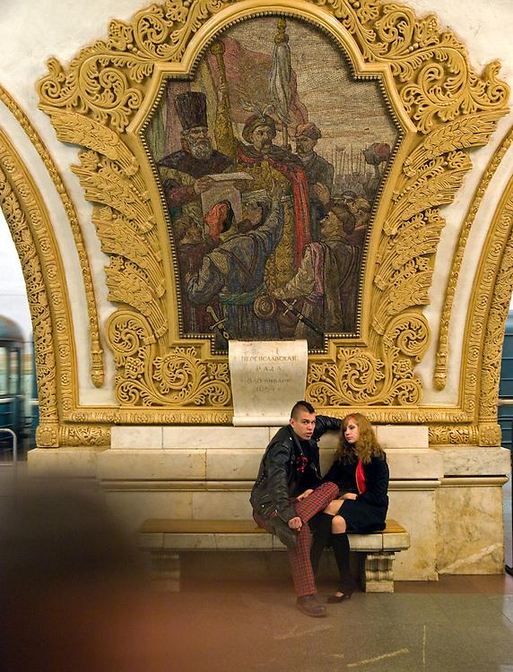 Junges Paar an der Moskauer Metrostation Kiewskaja. Die Station Kiewskaja befindet sich unter dem Kiewer Bahnhof. Hier laufen drei Linien zusammen. Sehenswert sind die Hallen der dunkelblauen Linie und die der Ringlinie. Mosaike beschwoeren die russisch-ukrainische Freundschaft.<br /> <br /> Young couple at the metro station Kiyevskaya which is a station on the Koltsevaya Line of the Moscow Metro. It is named for the nearby Kiyevsky Rail Terminal. Kievskaya features low, square pylons faced with white marble and surmounted by large mosaics by A.V. Myzin celebrating Russo-Ukrainian unity.