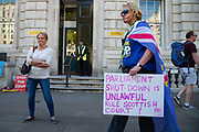 Anti Brexit protester holds a sign reading Parliament Shut Down Is Unlawful Rule Scottish Court outside the Cabinet Office as the Supreme Court sits for day two of the hearing on the legality of the suspenion of parliament on 18th September 2019 in London, United Kingdom. Supreme Court judges will decide if Prime Minister Boris Johnson acted unlawfully in advising the Queen to prorogue parliament.