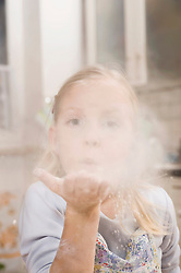 Girl blowing flour