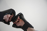 Karate gloves black sparring mitts against white wall background