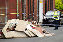© Licensed to London News Pictures. 27/06/2012. Oldham , UK . A large explosion , believed to be caused by gas , has brought down at least one house in an Oldham terrace . A police officer stands guard near to a pile of debris . Photo credit : Joel Goodman/LNP