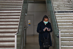 © Licensed to London News Pictures. 15/03/2020. London, UK. A woman wearing a face mask and plastic gloves at Stratford station amid an increased number of coronavirus (COVID-19) cases in the UK. 21coronavirus victims have died and 820 cases have tested positive of the virus in the UK of which 167 in London. Photo credit: Dinendra Haria/LNP